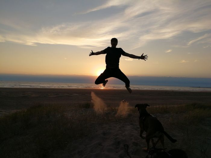 Dog One Man Only Pets Beach Only Men Full Length One Person Silhouette Jumping Sunset Adult Adults Only People Sand Sea One Animal Men Outdoors One Young Man Only Domestic Animals The Week On EyeEm EyeEm Selects Your Ticket To Europe Ijmuiden Aan Zee IJmuiden Second Acts