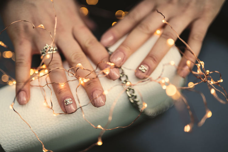 Cropped Hands With Illuminated String Lights And Purse On Table