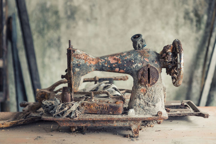 Close-up of damaged sewing machine on table in abandoned home