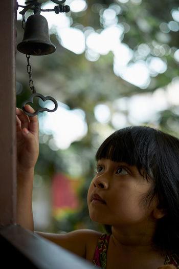 Close-up of girl holding bell seen through door
