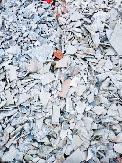 High angle view of garbage on metal crack tiles