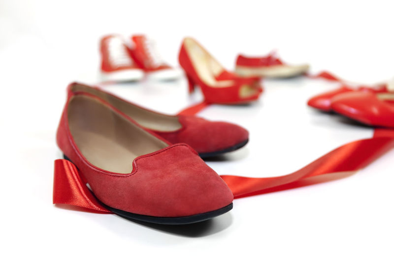 Red shoes women of various models, are based on a white floor and are joined by a red ribbon, which is the common thread that unites them: violence against women, symbolized by red shoes. Homicide Symbol Violence Close-up Elégance Fashion Femicide High Heels Murder; No People Pair Red Red Shoes Shoe Studio Shot Two Objects White Background