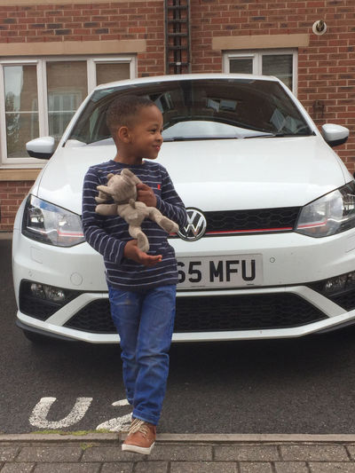 Boy holding toy while standing by car