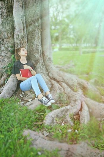 Woman with book leaning on tree at park