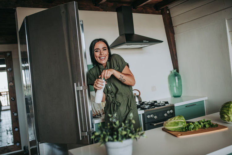 Woman holding food while standing at home