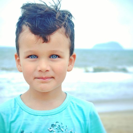 Close-up portrait of boy standing at beach against sky