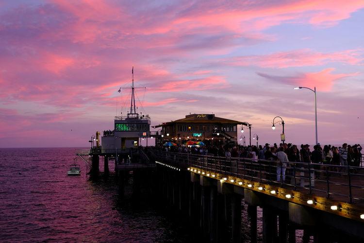 Illuminated Pier Over Sea Against Sky At Sunset