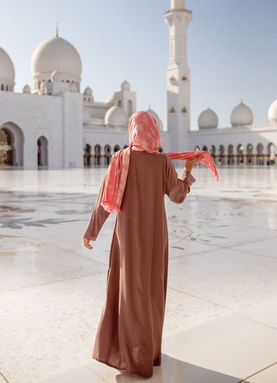Rear View Of Woman Standing At Sheikh Zayed Mosque During Sunny Day