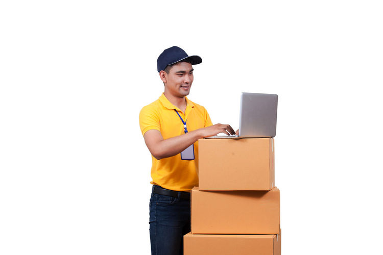 Smiling delivery man using laptop by cardboard boxes against white background