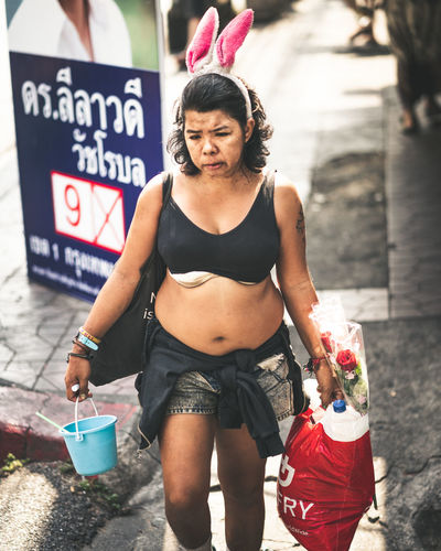 A lady walking in Bangkok Poverty Social Issues Bunny Ears  Homeless Homelessness  Woman Bags Bucket Alcoholic Drink Shopping Confused Day Real People Three Quarter Length One Person Front View Focus On Foreground Adult City Footpath Street Photography Economic