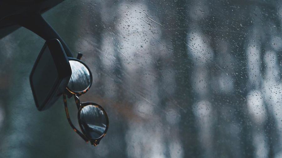 Close-up of sunglasses with raindrops on rainy day