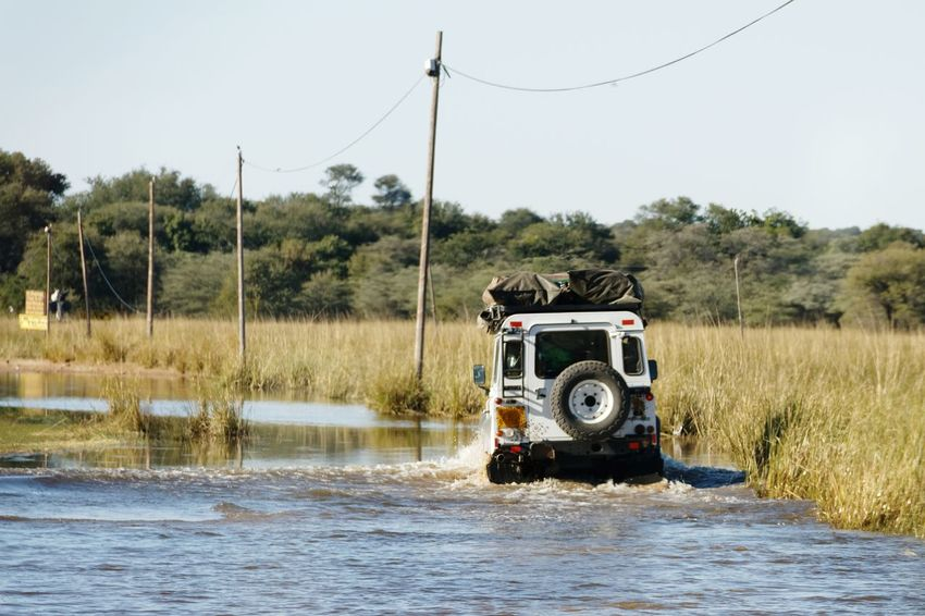 4x4 vehicle driving through flooded road Landrover  Namibia Africa Aftican Road Caprivi Okovango Flood Flooding Flooded Road Driving Through EyeEm Selects Water Tree Spraying Social Issues Rural Scene Sky Off-road Vehicle 4x4 Sports Utility Vehicle Tire Track Dirt Track Dirt Road