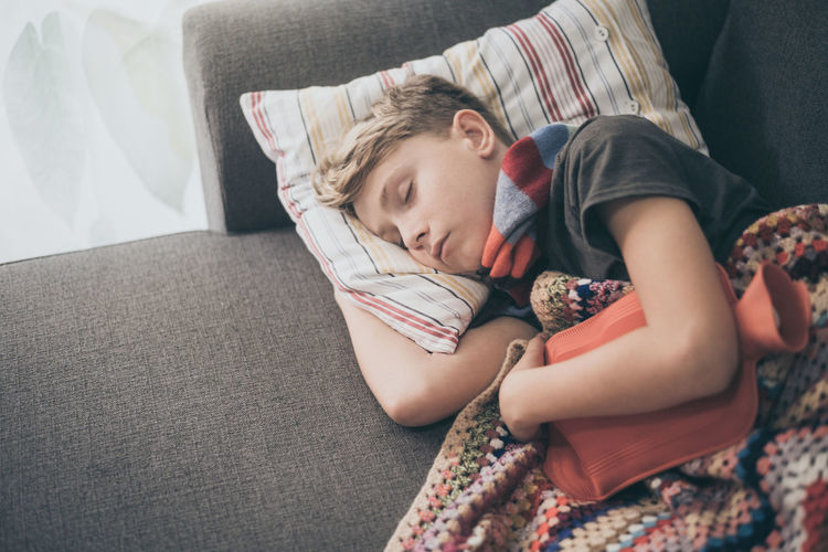 High angle view of boy sleeping on sofa at home