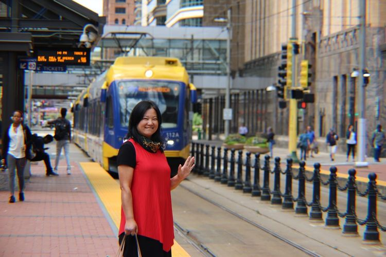 Portrait of mature woman smiling while standing at railroad station platform in city