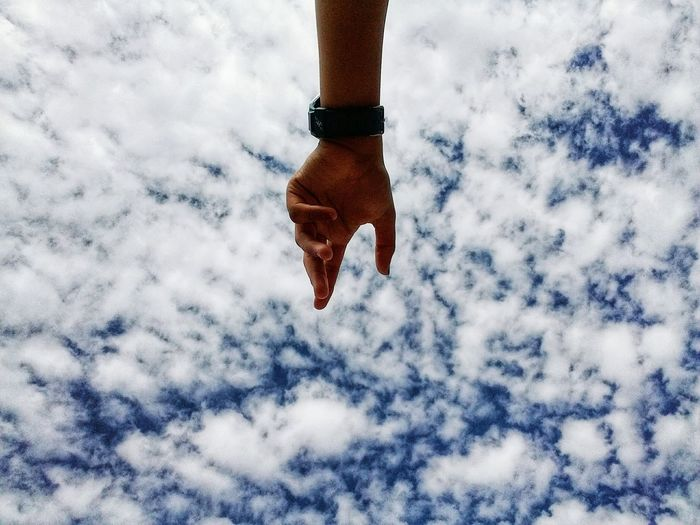 Cropped hand gesturing against cloudy sky