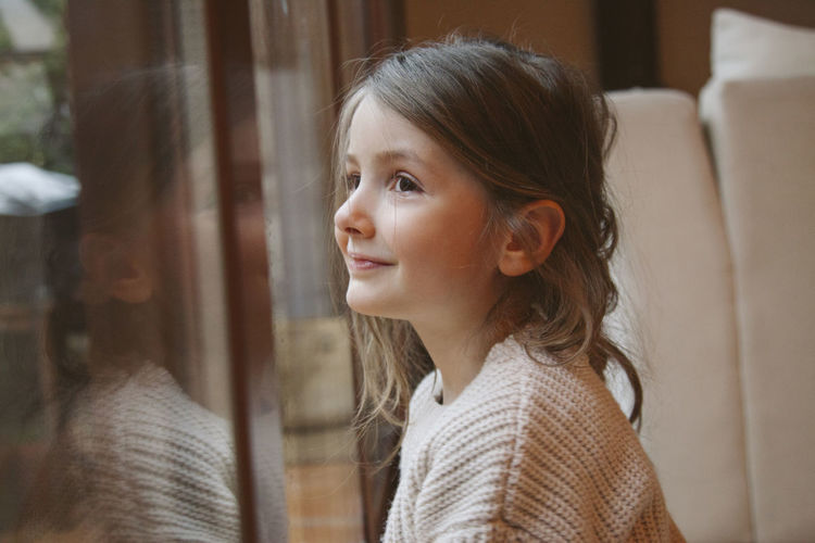 Close-up of cute girl looking through window at home