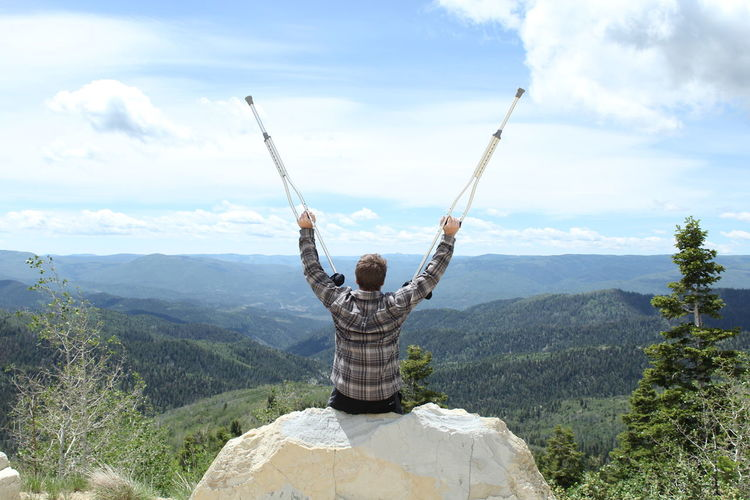 Rear view of man holding crutches while sitting on rock against mountains