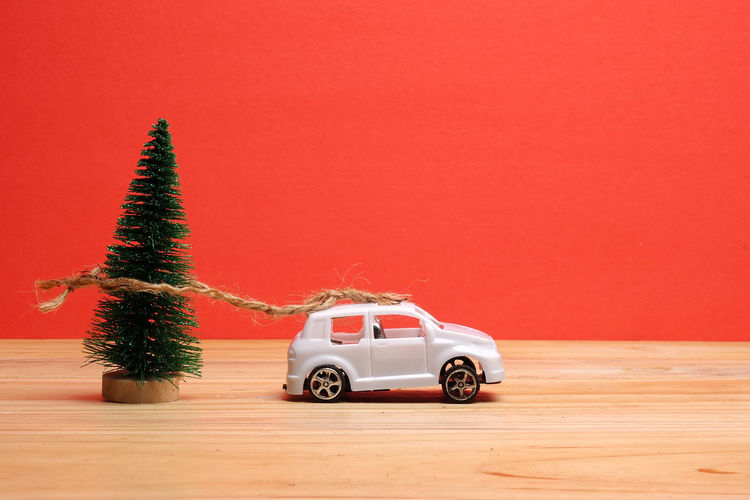 Close-Up Of Christmas Tree By Toy Car On Table Against Red Background