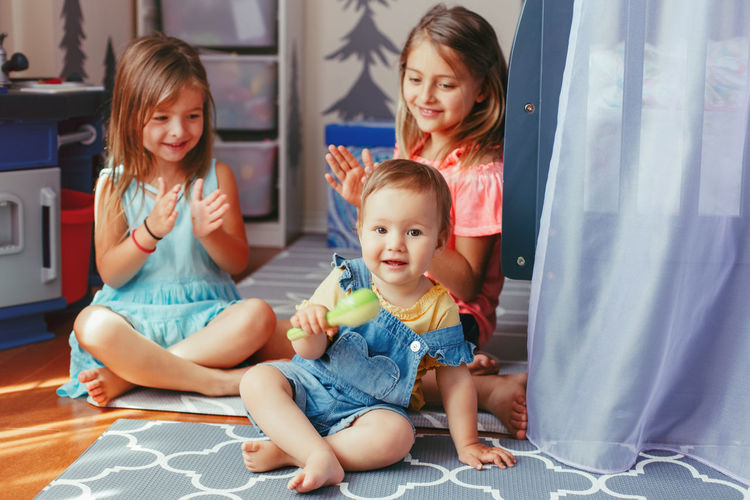 Sisters clapping while looking at brother in playroom