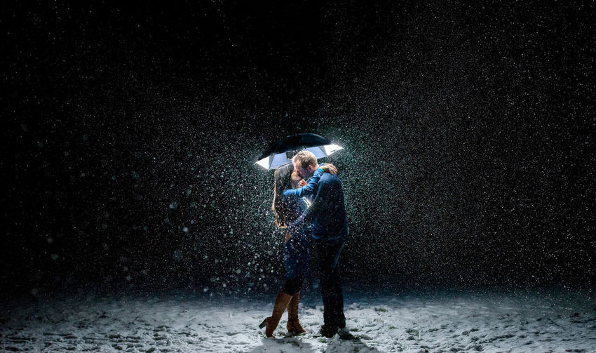 Couple standing out in the snow kissing