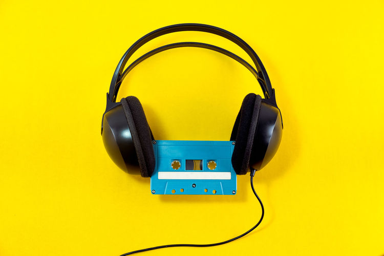 Top view of Headphone and blue classic tape cassette against yellow isolated background. Listening music theme. Headphone Tape Cassette Music Song Sing Musical Listen Radio Audio Sound Record Old Yellow Disco Stereo Media Karaoke Rock Retro Design Vintage Background Headphones Blue Compact Party Blank Play Creative Colorful Pastel Overhead Dance Minimalism Minimal Classic Copy Track Mix Top View Playlist Concept Player Analogue Listening Broadcasting Isolated Broadcast Label