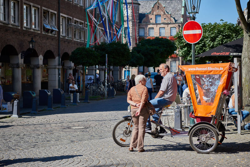 DUESSELDORF, GERMANY - AUGUST 17, 2016: Unidentified riksha driver chats with an unidentified lady in Duesseldorf Altstadt Altstadt Atmosphere Bar Blu Sky City Life City Street Daytime Düsseldof High Resolution Lifestyles NRW Outdoors People R Relaxing Restaurant Rheinland-Pfalz  Rhine Promna S Shopping Tourism Travel Destinaton