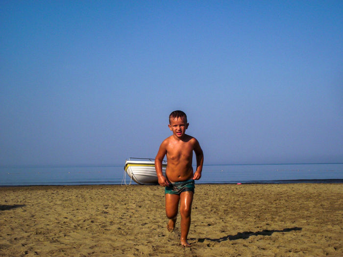 Full Length Of Shirtless Boy Walking At Beach Against Clear Sky