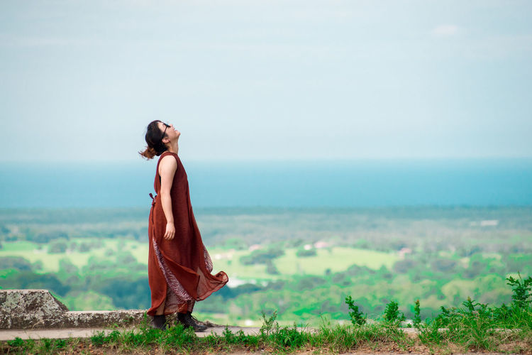 Side view of young woman wearing sunglasses standing on observation point against cloudy sky