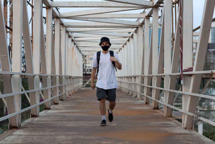 Young millennial walking on footbridge while wearing a protective mask to prevent covid-19 infection