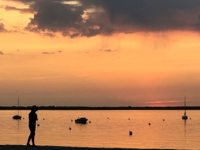 Silhouette woman standing on sea against sky during sunset