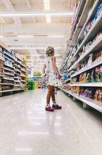 Full Length One Person Childhood Indoors  Women Real People Lifestyles Child Casual Clothing Store Girls Standing Supermarket Hair Shelf Choice Shopping Hairstyle Innocence Consumerism