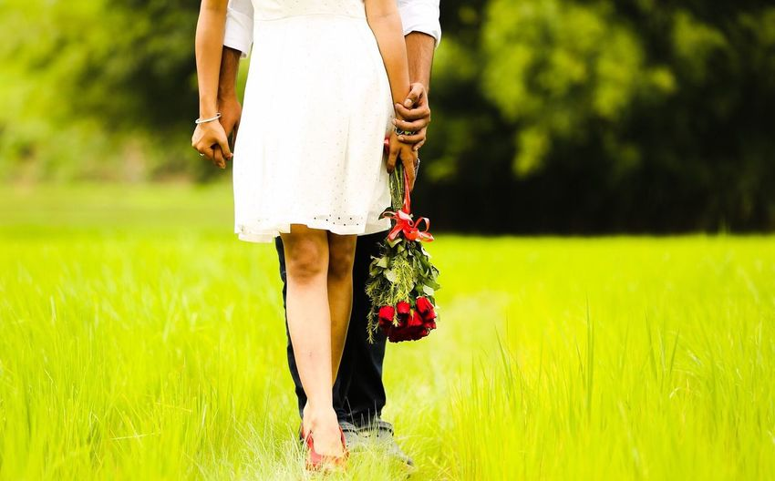 Low section of couple standing on grassy field