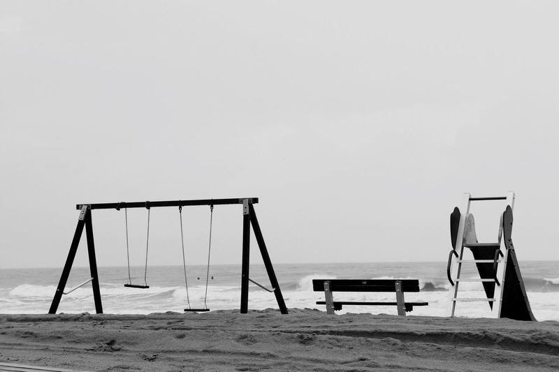 Swing and slide by bench on sand at beach against clear sky