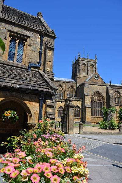 Townscape in the historic market town of Sherborne in Dorset, England, showing the Almshouses in the foreground and the Abbey in the background. Almshouses Blooms Building Exterior Built Structure Church Architecture Dorset England English Famous Place Flowers Historical Building Historical Buildings Historical Monuments Historical Sights Quaint Places Sherborne Sherborne Abbey Summer Summertime