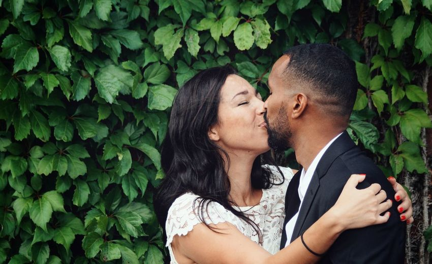 Close-up of couple kissing against plants