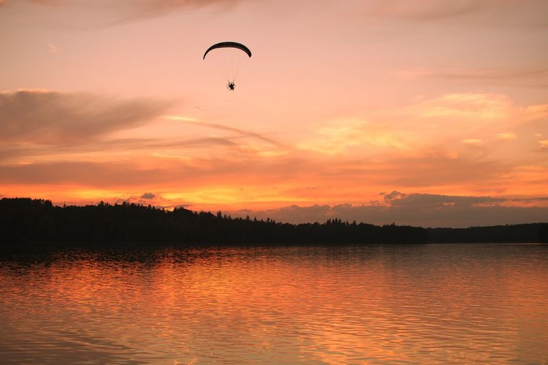 Paragliding Parachute Sunset Sky Water Flying Beauty In Nature Orange Color Silhouette Cloud - Sky No People Tranquil Scene Tranquility Scenics - Nature