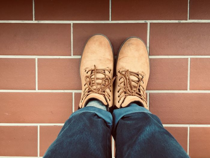 Low Section Of Man Wearing Shoes While Standing On Tiled Floor
