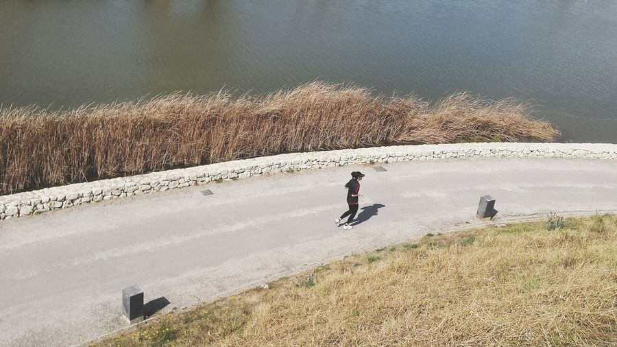 High angle view of woman jogging on road