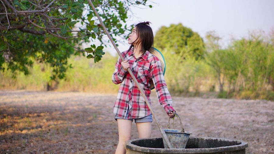 Young woman putting pole in well at farm