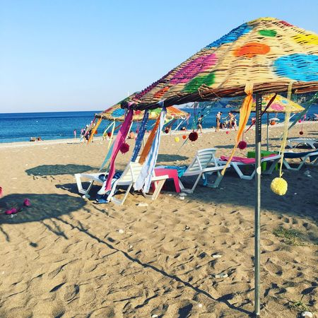 Beach Sand Sea Beach Umbrella Shore Water Nature Horizon Over Water Vacations Outdoors Summer Sun Lounger Day Beauty In Nature Canopy No People Multi Colored Tranquil Scene Sunlight Scenics