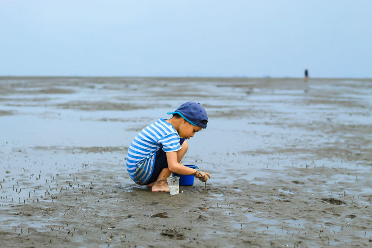 Full Length Of Boy Playing With Sand At Beach