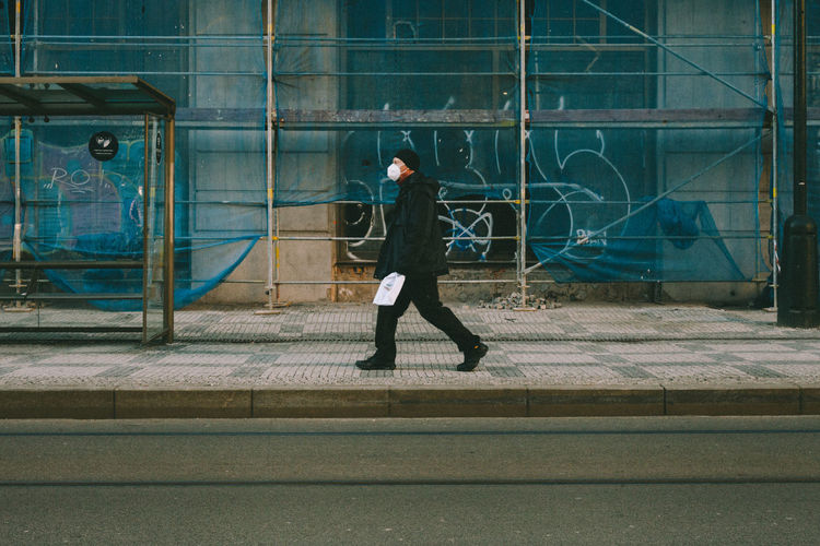 Full length side view of man walking against building in city