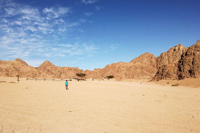 Man Standing On Sand Dune In Desert Against Blue Sky
