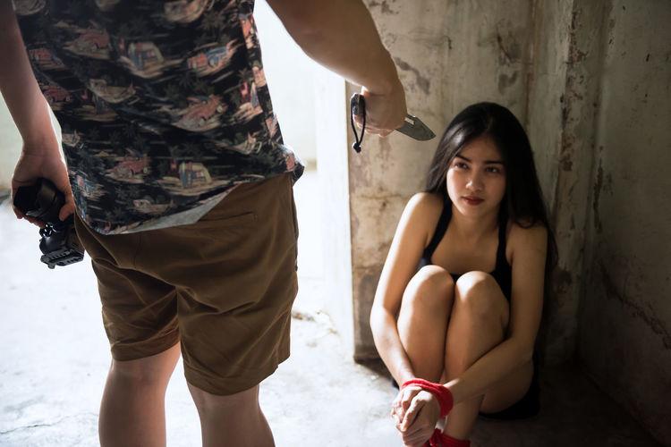 Hopeless woman sitting by wall