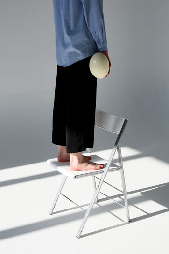 Indoors  Women Low Section Studio Shot Casual Clothing Human Body Part Lifestyles Holding Clothing Real People Egg Chair Light And Shadow Light Sunlight Feet Legs Fashion Girl Minimal Minimalism Minimalist Ostrich Egg Cropped