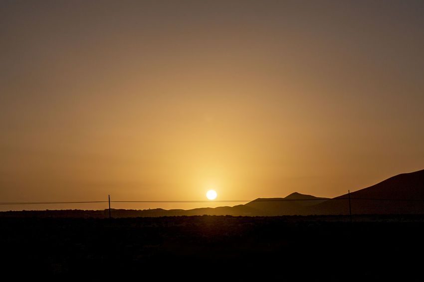 At Las Dunas Clear Sky Desert Silhouettes Sunlight Sunrise - Dawn Back Lit Beauty In Nature Dusk Hill Landscape Mountain Nature No People Orange Color Outdoors Scenics Silhouette Sky Summer Sun Sunset Tranquil Scene Tranquility Yellow