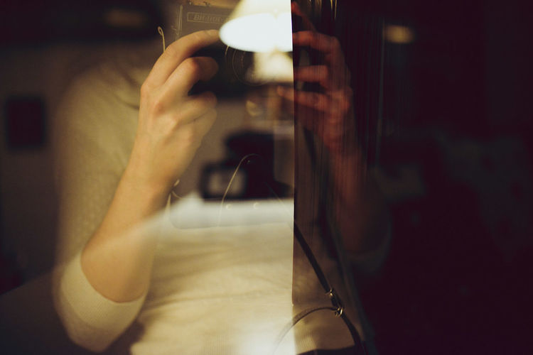 Double exposure of illuminated lamp and woman holding vintage camera