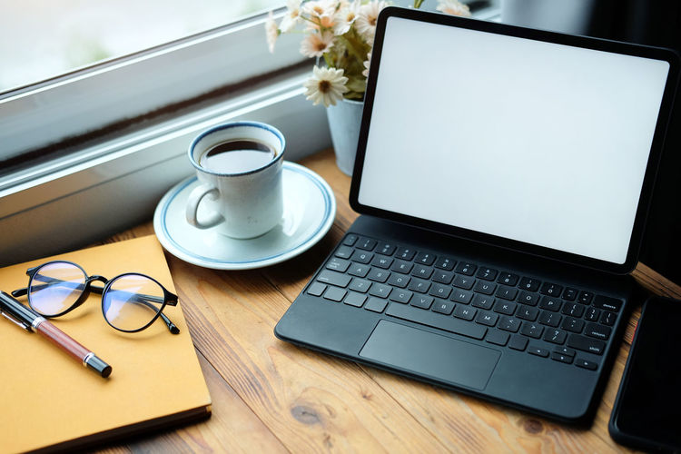 Coffee cup and laptop on table