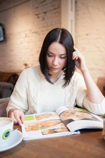 Woman looking at menu while sitting in restaurant