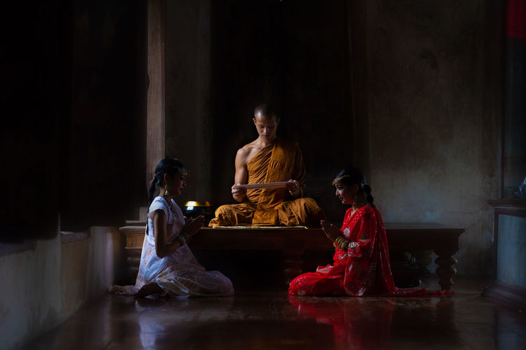 Women praying while sitting by monk in temple